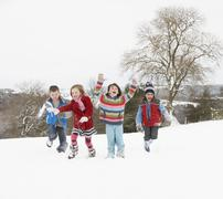 group of children having fun in snowy countryside - stock photo