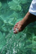 Woman's foot outdoors dipping into water (selective focus) - stock photo