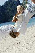 Couple on a swing outdoors at the beach Stock Photos