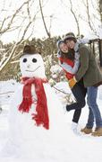Teenage couple building snowman Stock Photos