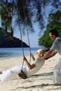 Man outdoors by a beach pushing a woman on a swing (selective focus) Stock Photos