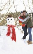 Teenage couple building snowman Stock Photos
