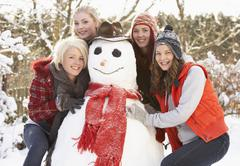 group of teenage girls building snowman - stock photo