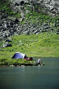 Camper outdoors at campsite by lake drinking beverage (far away) Stock Photos