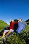 Woman outdoors at campsite by lake yawning and stretching Stock Photos