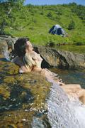 Couple outdoors by campsite relaxing in stream - stock photo