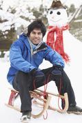 Teenage boy with sledge next to snowman Stock Photos