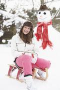 Teenage girl with sledge next to snowman Stock Photos