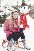 teenage girl with sledge next to snowman - stock photo