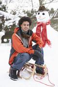 Stock Photo of man with sledge next to snowman