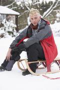 teenage boy with sledge next to snowman - stock photo
