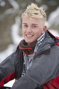 Teenage boy wearing winter clothes in snowy landscape Stock Photos