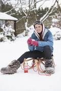 Teenage girl with sledge next to snowman with flask and hot drink Stock Photos