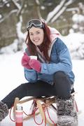 teenage girl with sledge next to snowman with flask and hot drink - stock photo