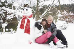 teenage couple in winter landscape next to snowman with flask and hot drink - stock photo