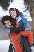 teenage boy giving girl piggyback in snowy landscape - stock photo