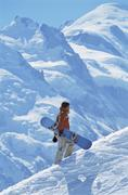 Snowboarder going up hill carrying board - stock photo