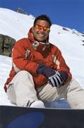 Snowboarder sitting on hill with board smiling (selective focus) - stock photo