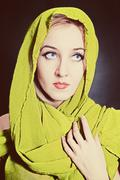 portrait of  beautiful young woman in bright, green head scarf - stock photo