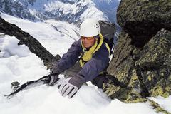 Mountain climber coming up snowy mountain Stock Photos