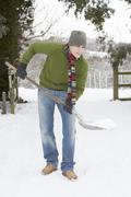 young man clearing snow from drive - stock photo