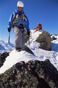 Two mountain climbers walking on snowy rocks (selective focus) Stock Photos