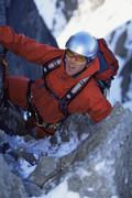 Stock Photo of Mountain climber going up snowy mountain (selective focus)