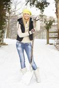 teenage girl clearing snow from drive - stock photo