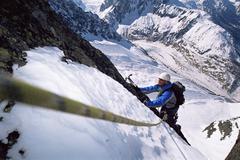Mountain climber going up snowy mountain - stock photo