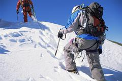 Two mountain climbers walking in snow (selective focus) Stock Photos