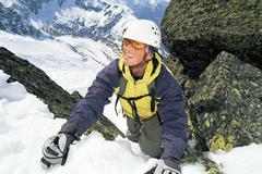 Vuorikiipeilijä tulossa lumisen vuoren hymyillen (valikoiva tarkennus) Kuvituskuvat