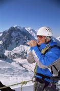 Mountain climber standing in snow on mountain warming up hands (selective focus) Stock Photos