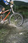 Man outdoors on trails riding bicycle (selective focus) - stock photo