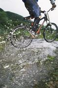 Man outdoors on trails jumping bicycle over puddles (selective focus) Stock Photos