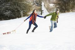 teenage couple pulling sledge across snowy field - stock photo