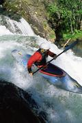 Kayaker in rapids going over waterfall (blur) Stock Photos
