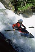 Kayaker in rapids going over waterfall (blur) - stock photo