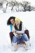 couple sledging through snowy woodland - stock photo