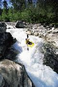 Kayaker in rapids going over waterfall - stock photo