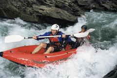 Two kayakers in rapids smiling (selective focus) Stock Photos