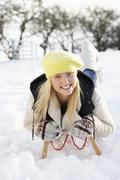 teenage girl riding on sledge in snowy landscape - stock photo