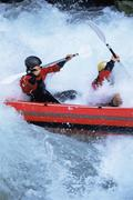 Two kayakers rowing in rapids - stock photo