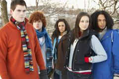 Stock Photo of group of teenage friends having fun in snowy landscape wearing ski clothing