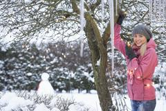 Teenage girl hanging fairy lights in tree with icicles in foreground Stock Photos