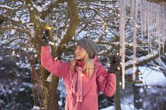 teenage girl hanging fairy lights in tree with icicles in foreground - stock photo