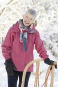 Senior woman holding sledge in snowy landscape Stock Photos