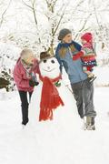 young girl with grandmother and mother building snowman in garden - stock photo