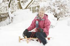 senior woman sitting on sledge in snowy landscape - stock photo