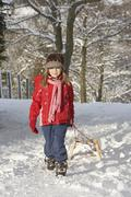young girl pulling sledge through snowy landscape - stock photo
