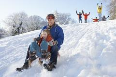 father and daughter having fun sledging down hill - stock photo